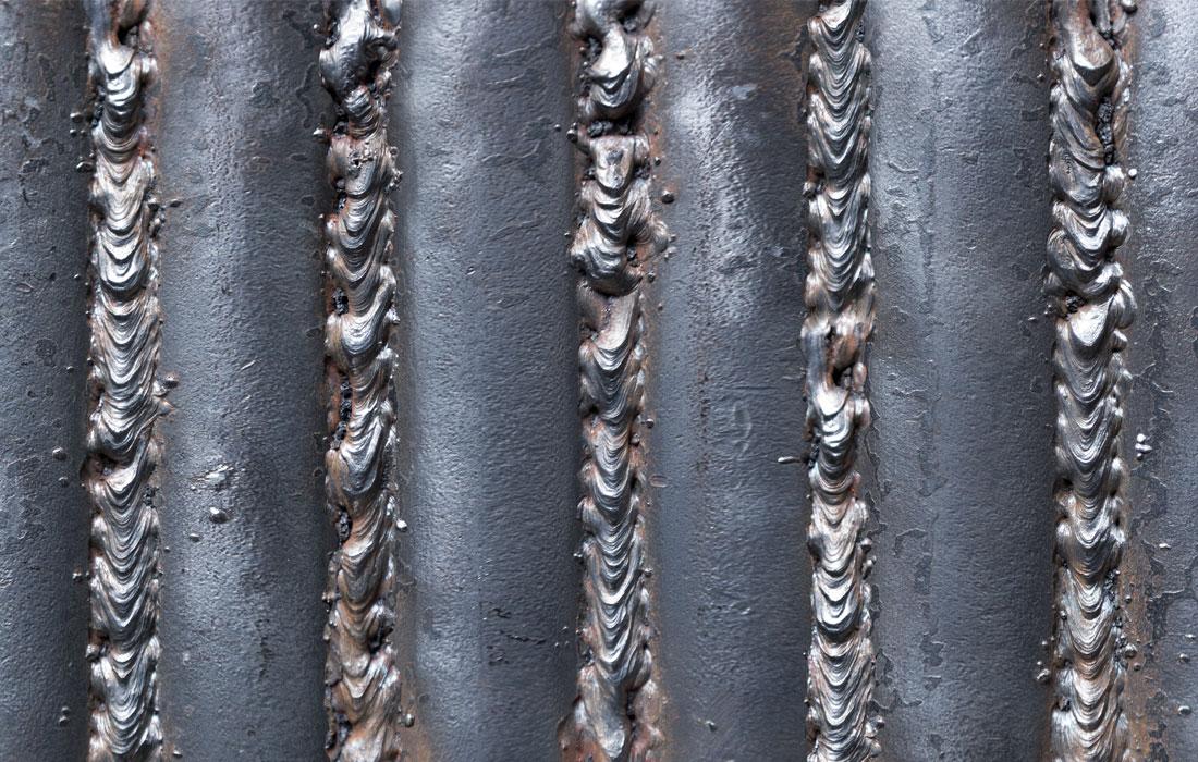 Primerísimo plano del proyecto M-B de José Carlos Balanza, dónde se ven unas varillas macizas de hierro unidas entre sí mediante cordones de soldadura. Museo de Arte Contemporáneo del Camino