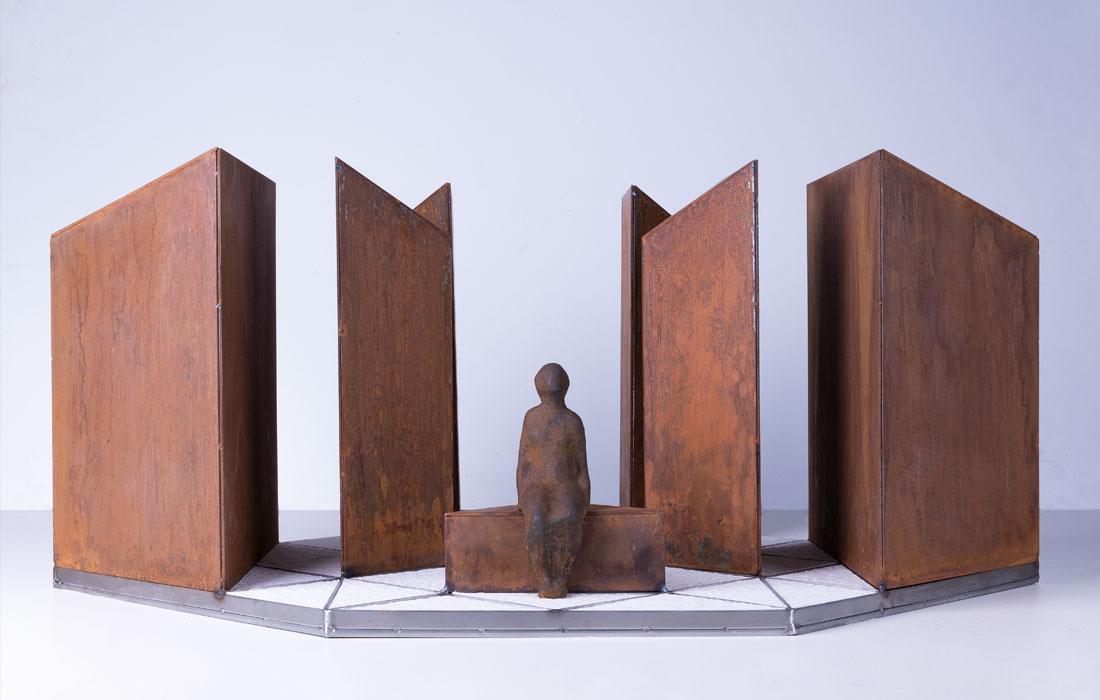 Vista frontal proyecto Diamante del artista Oscar Cenzano para el Museo de Arte Contemporáneo del Camino. Conjunto escultórico formado por unos prismas de base triangular de acero corten sobre una base de losas de cemento armado texturizado de forma triangular y una figura de una persona de hierro fundida sentada