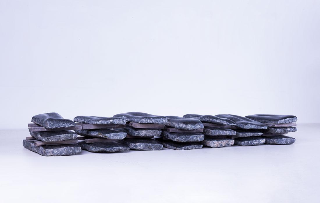 Vista frontal del proyecto Noites de Piedra de la artista Pamen Pereira para el Museo de Arte Contemporáneo del Camino. Conjunto de veintiun lechos de piedra de granito negro apilados en 7 columnas de tres laudas cada una, separadas entre ellas por listones de madera, formando un conjunto de 9 m de largo por 1,30 m de alto por 2 m de profundidad