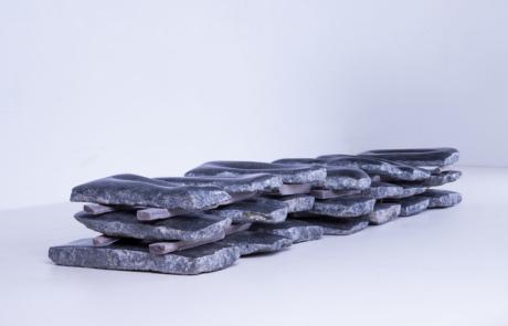 Vista lateral del proyecto Noites de Piedra de la artista Pamen Pereira para el Museo de Arte Contemporáneo del Camino. Conjunto de veintiun lechos de piedra de granito negro apilados en 7 columnas de tres laudas cada una, separadas entre ellas por listones de madera, formando un conjunto de 9 m de largo por 1,30 m de alto por 2 m de profundidad