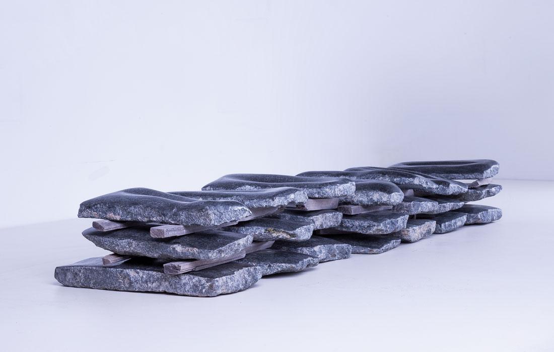 Proyecto Noites de Piedra de la artista Pamen Pereira para el Museo de Arte Contemporáneo del Camino. Conjunto de veintiun lechos de piedra de granito negro apilados en 7 columnas de tres laudas cada una, separadas entre ellas por listones de madera, formando un conjunto de 9 m de largo por 1,30 m de alto por 2 m de profundidad